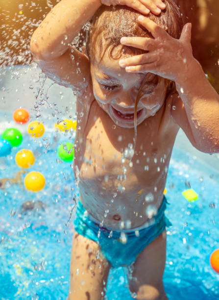 happy child in the pool - children play water park stock photos and pictures