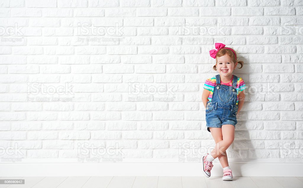 Happy child little girl laughing at blank brick wall stock photo