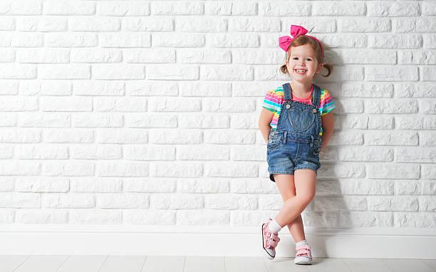 glückliches kind, kleines mädchen lachen im leere ziegelwand - sprüche kinderlachen stock-fotos und bilder