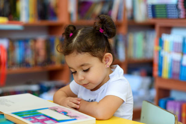 Happy child little girl reading a book. Little Girl Indoors In Front Of Books. Cute Young Toddler Sitting On A Chair Near Table and Reading Book. Child reads in a bookstore, surrounded by colorful books. Library, Shop, Shelving In Home. baby girls stock pictures, royalty-free photos & images