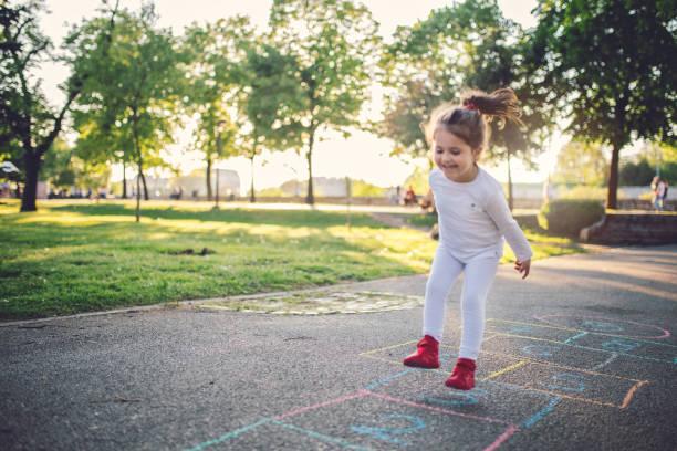 glückliches kind auf einem spielplatz - himmel und hölle spiel stock-fotos und bilder
