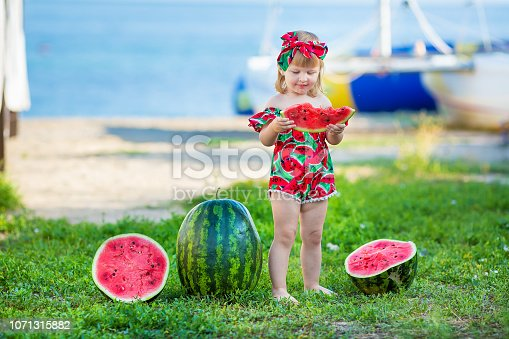 istock Happy child on the sea tropical beach with watermelon in hands enjoy life time weekend wearing fancy stylish retro swim wear bikini and bandana with yacht on background 1071315882