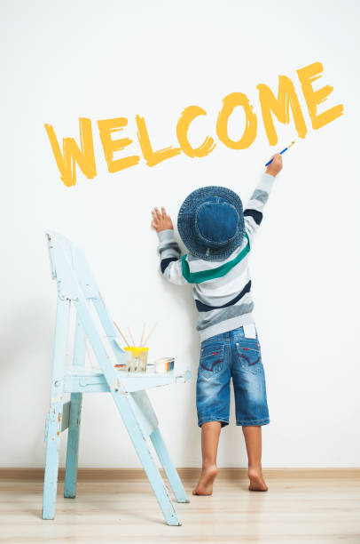 happy child paints with paint. - welcome stock photos and pictures