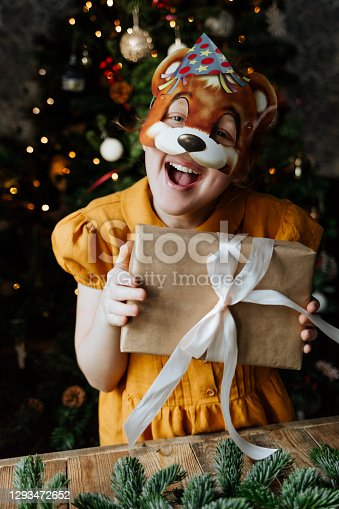 Happy child under the Christmas tree with a gift.