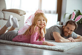I am fairy. Portrait of charming little girl is lying on soft carpet at home. She is looking at camera and smiling while wearing crown and wings. Her father is relaxing on flooring next to her