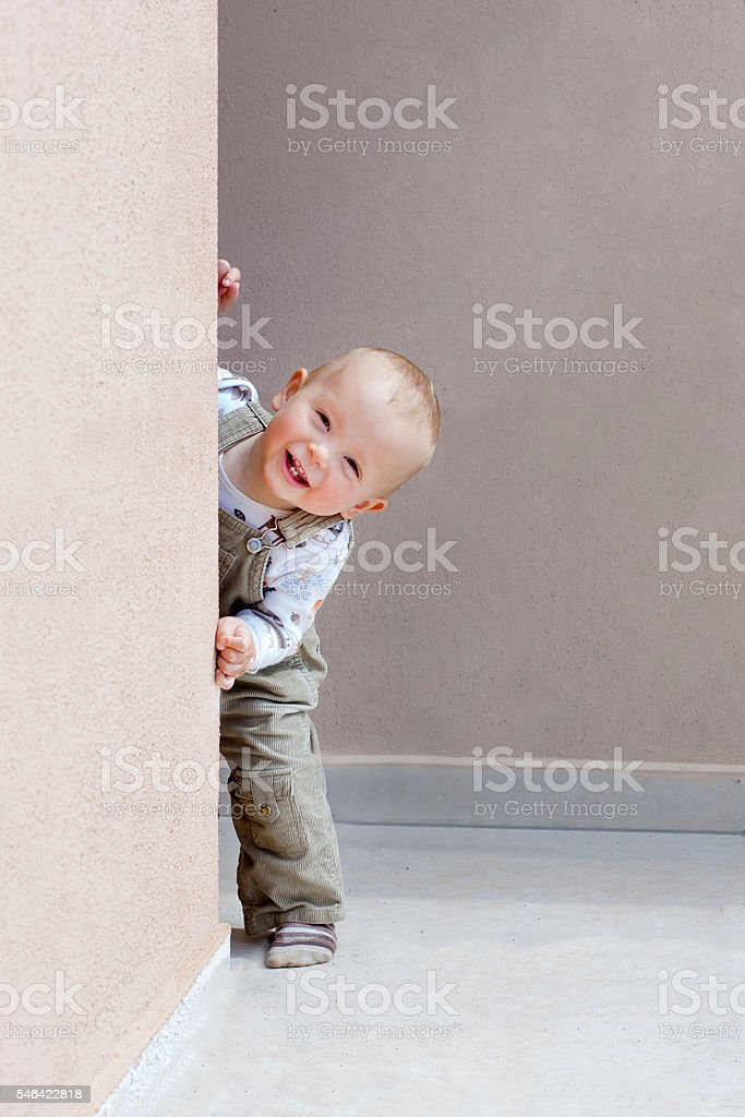 Happy child playing hide and looks out of the corner. stock photo