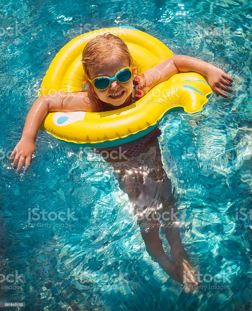 Happy child playing in swimming pool stock photo