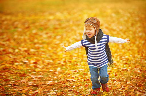 istock happy child playing pilot aviator outdoors in autumn 489529076