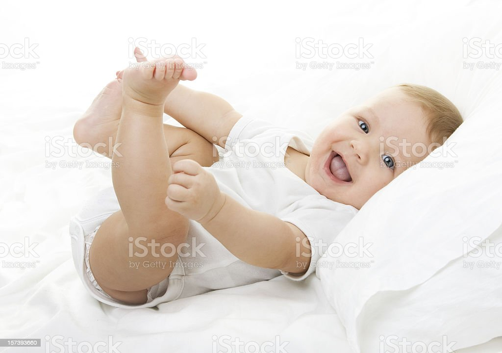 Happy Child playing with his feet stock photo