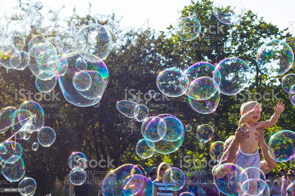 Happy child playing with soap bubbles against blue sky stock photo