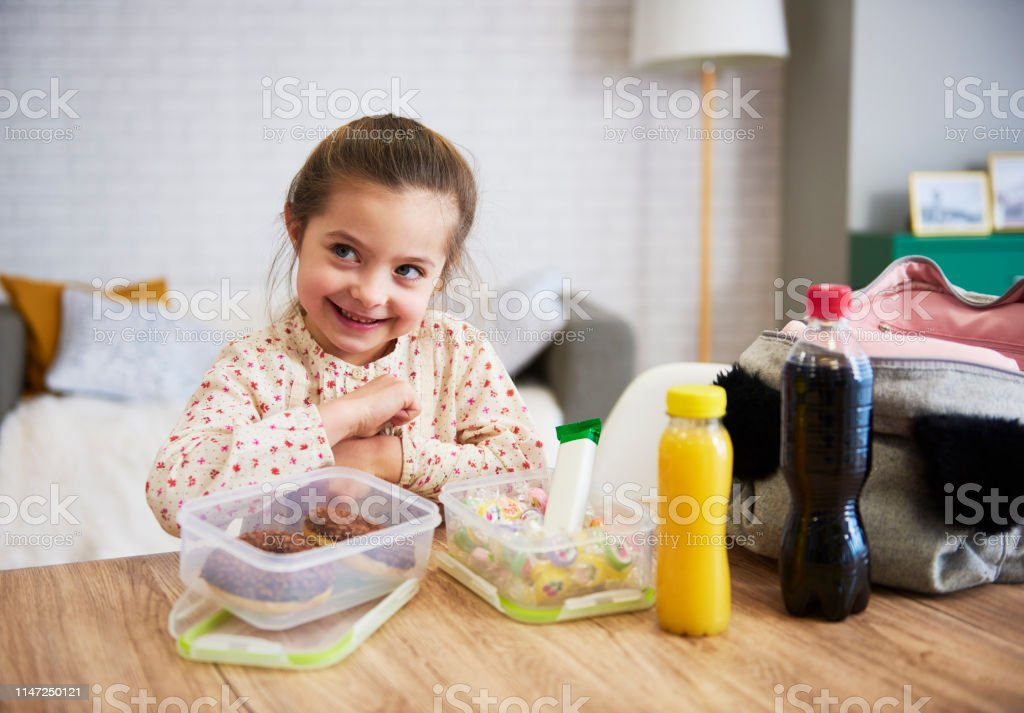 Happy child preparing lunch box with sweets