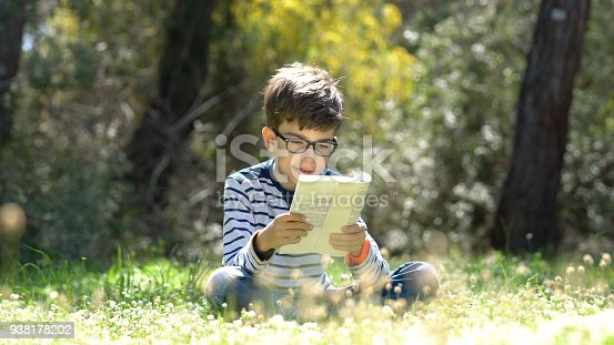 istock Happy child reading a book in forest 938178202