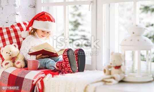 istock happy child reading a book while at a winter window 627164012