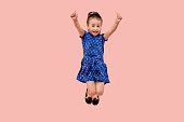A happy child rejoices in victory with his hands raised up and jumps up. The concept of winning. Human emotion. In a blue dress with a small star print. Pink isolated background.