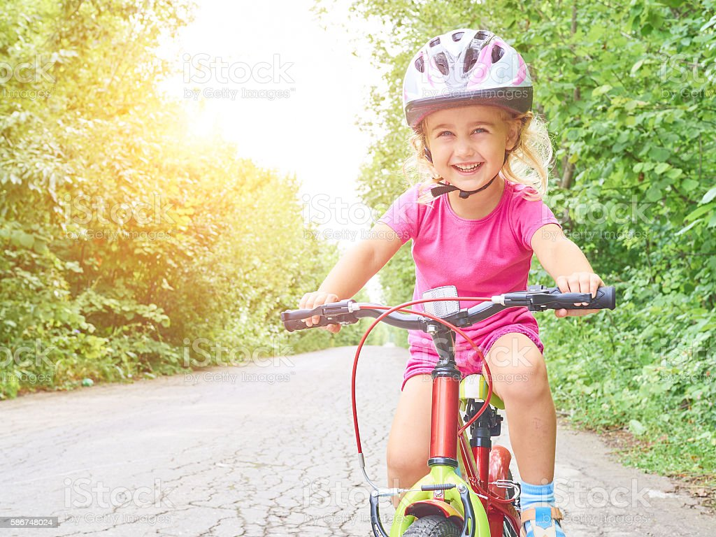 Happy child riding a bike in outdoor. Cute kid in safety helmet...