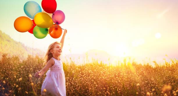 Glückliches Kind läuft mit Luftballons im Feld bei Sonnenuntergang – Foto