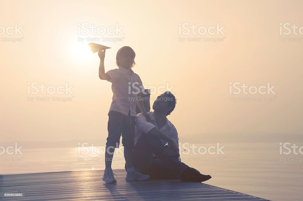 happy child showing his father his new paper airplane stock photo
