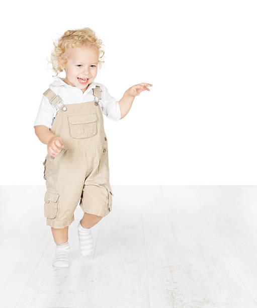 Happy child smiling, running on white floor stock photo