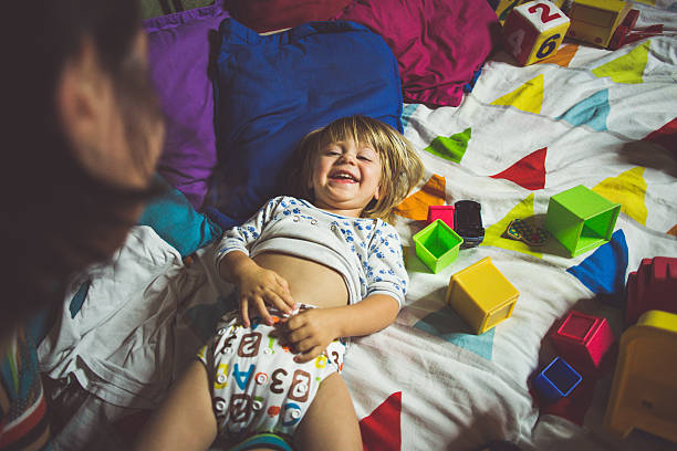 happy child smiling while his mother changing diapers - wickelkissen stock-fotos und bilder