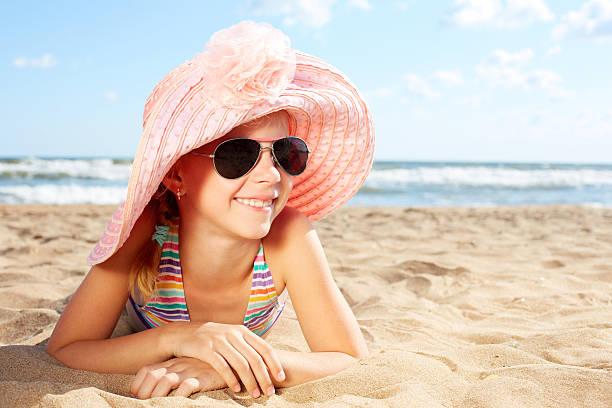 Happy child sunbathes on sand near the ocean stock photo