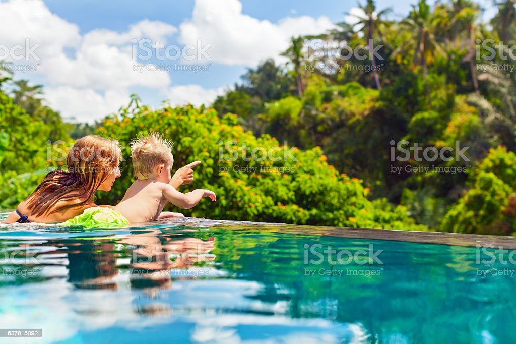 Happy child swimming in with mother infinity pool stock photo