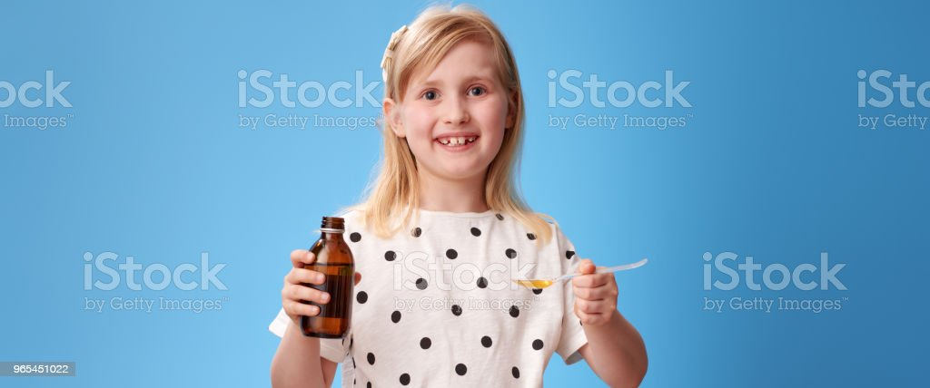 happy child taking spoon of children's suspension on blue royalty-free stock photo