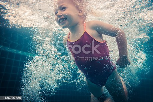 Happy joyful child toddler swimming underwater in swimming pool