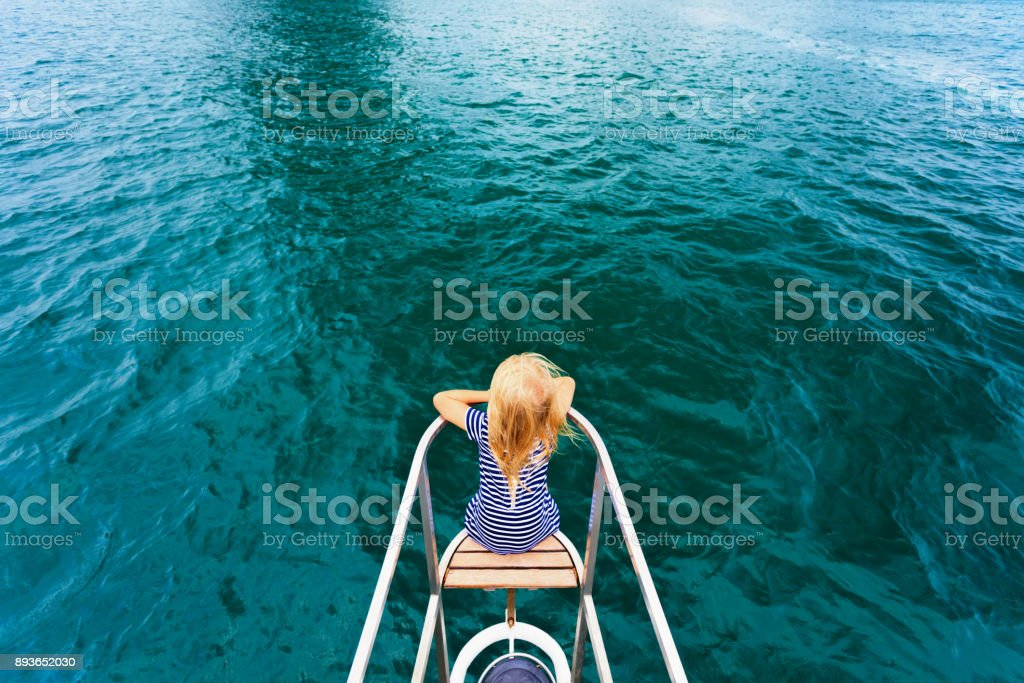 Happy child traveling on sailing yacht stock photo