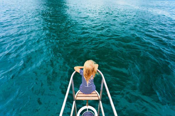 Happy child traveling on sailing yacht stock photo