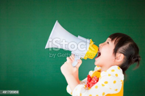 991060890 istock photo happy child  using a megaphone with blackboard 491705959