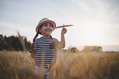 Gorgeous little toddler girl with a hat, playing in meadow with her airplane model.