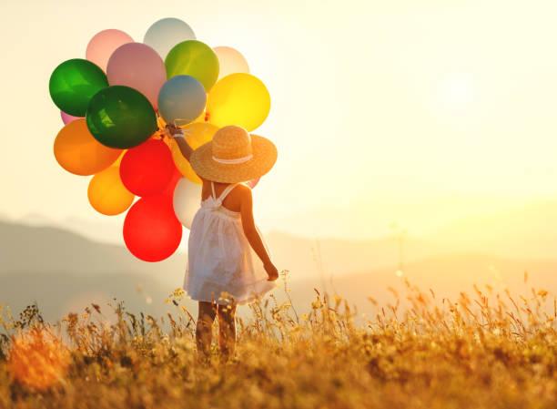 . glückliches Kind mit Luftballons bei Sonnenuntergang im Sommer – Foto
