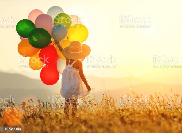 Photo of . happy child with balloons at sunset in summer