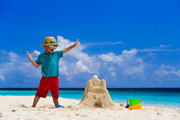 heureux enfant avec construction de château de sable sur la plage - chateau de sable photos et images de collection