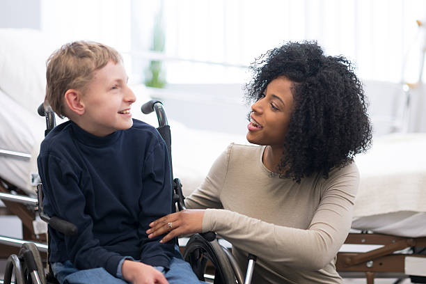 Happy Child with Cerebral Palsy A physical therapist is working with a child in the hospital that has cerebral palsy. paraplegic stock pictures, royalty-free photos & images