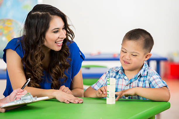 happy child with down syndrome accomplishing task in school - school counselor stock photos and pictures