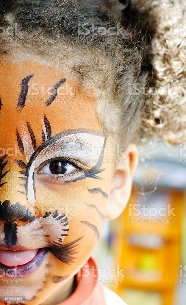 Happy Child with her tiger face paint. stock photo