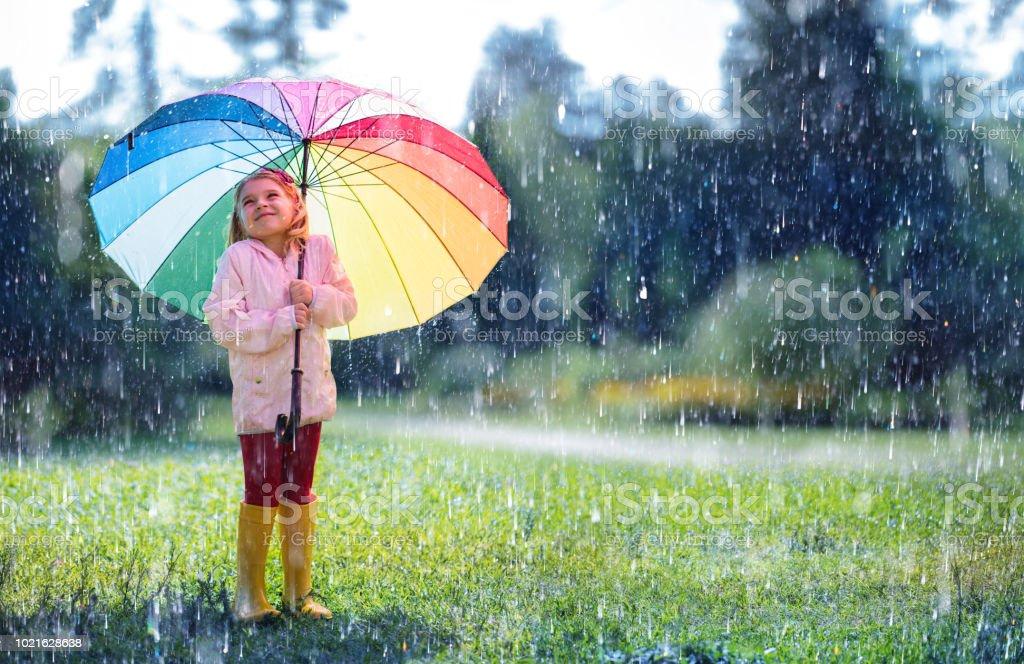 Enfant heureux avec parapluie arc-en-ciel sous la pluie - Photo