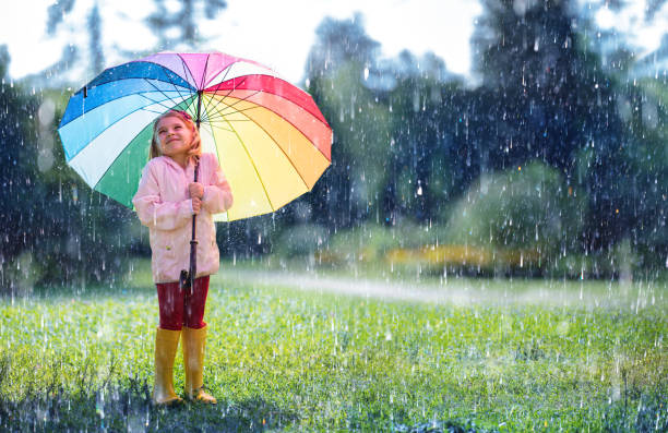 happy child with rainbow umbrella under rain - deszcz zdjęcia i obrazy z banku zdjęć
