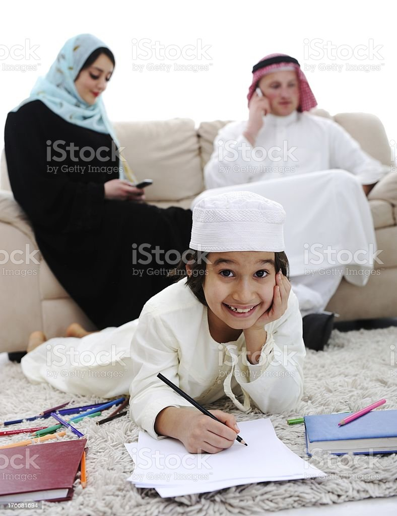 Happy child working on homework at home with his family royalty-free stock photo