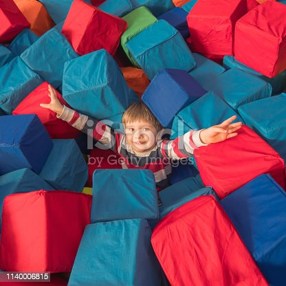 544818734 istock photo Happy childhood concept. Boy playing with soft blocks in entertainment center. Kid in good mood holding hands widely up expressing happiness. 1140006815