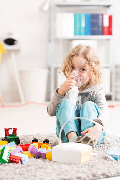 Happy childhood despite disease Small boy doing inhalation, sitting on a floor with toys in light interior despite stock pictures, royalty-free photos & images