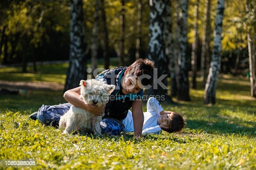 Brothers have a fun in city park with cute white dog