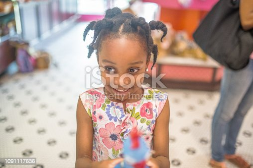 Happy, smiling, adorable little girl, 4 years old, with childhood enthusiasm and joy. In some kind of shop standing next to someone, her mother perhaps. Anticipation and excitement bubbling over
