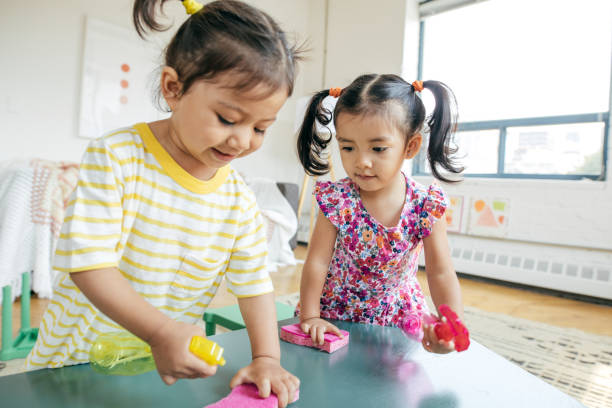 Happy childhood 2 years old girl kids cleaning up toys stock pictures, royalty-free photos & images
