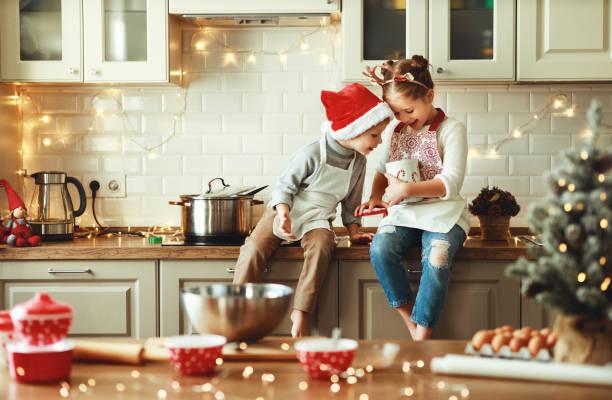 gelukkige kinderen jongen en meisje bakken kerstkoekjes - christmas family stockfoto's en -beelden