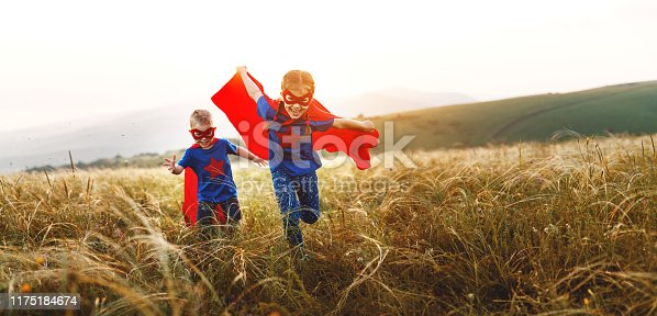 happy children boy and girl in costumes of superheroes in the outdoor