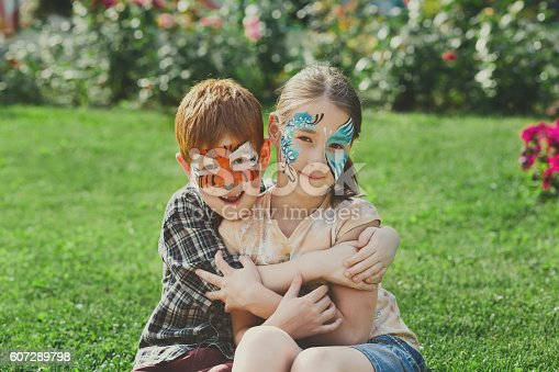 istock Happy children, boy and girl with face paint in park 607289798