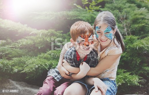 istock Happy children, boy and girl with face paint in park 610148882