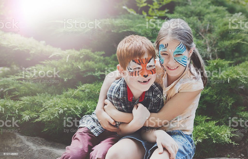 Happy children, boy and girl with face paint in park stock photo